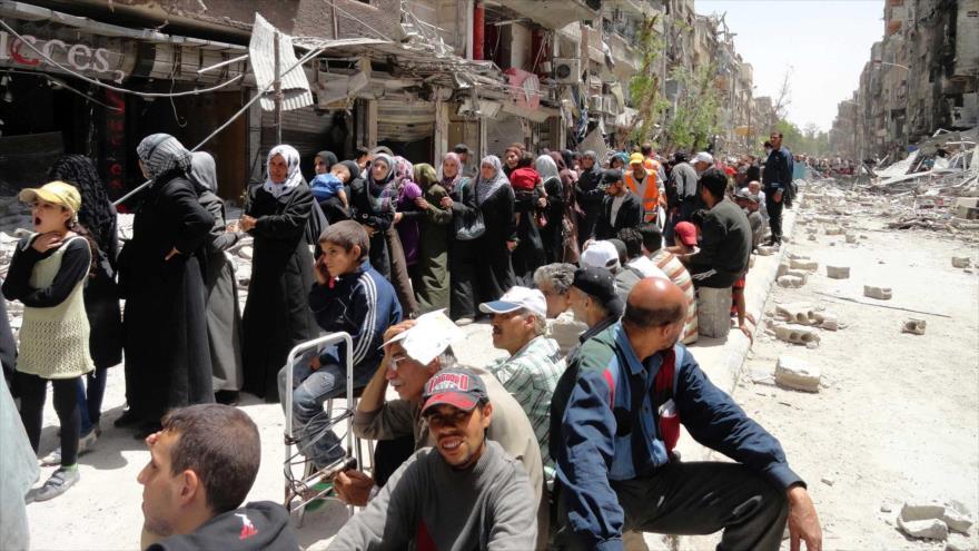 Refugiados palestinos hacen filas en el campamento de refugiados palestinos Yarmouk de Siria para recibir ayuda alimentaria.