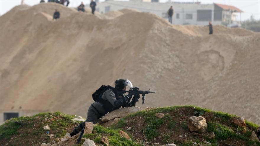 Un guardia fronterizo israelí apunta contra manifestantes palestinos en el norte de Ramalá, en la ocupada Cisjordania, 12 de enero de 2018.