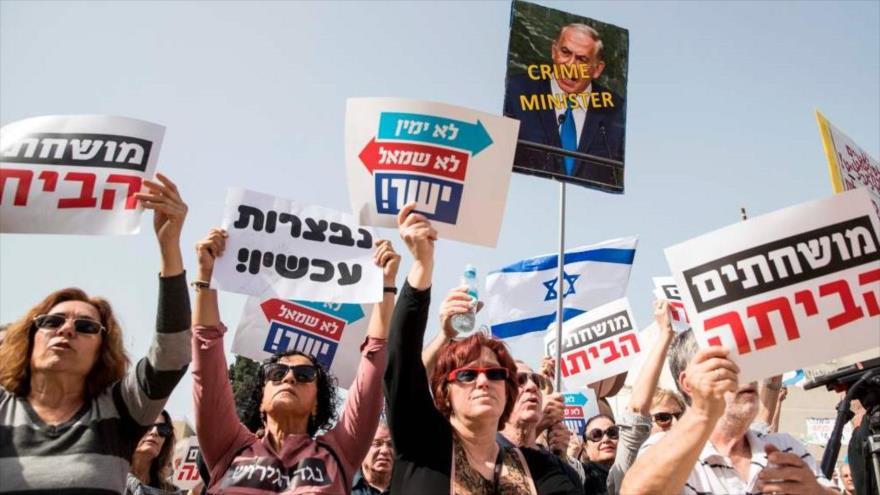 "Israelíes con lema ""corrupto vete a casa"" protestan contra el primer ministro Benyamin Netanyahu, en Tel Aviv, 18 de febrero de 2018."