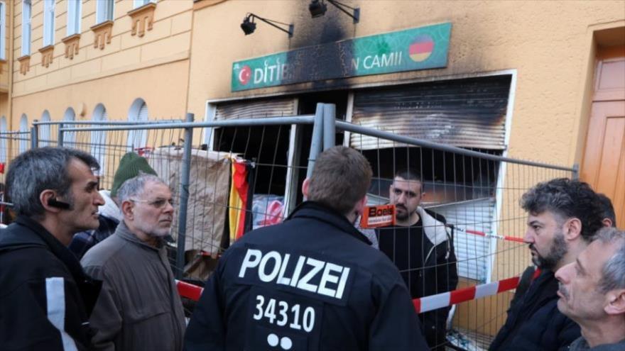Un policía habla con un miembro de la mezquita Koca después de haber sido incendiada, Berlín, Alemania, 11 de marzo de 2018.