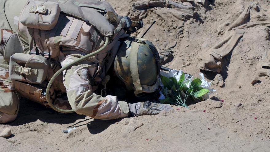 Un soldado iraquí rinde homenaje a uniformados asesinados por Daesh descubiertos en una fosa común.