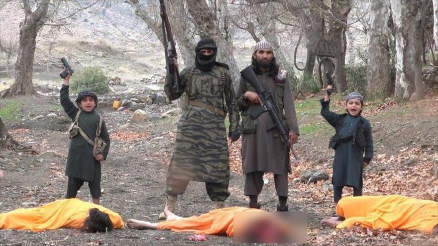 Tres víctimas de Daesh son ejecutadas, dos de ellos soldados del Ejército de Afganistán, a manos de los dos menores en los extremos de la imagen.