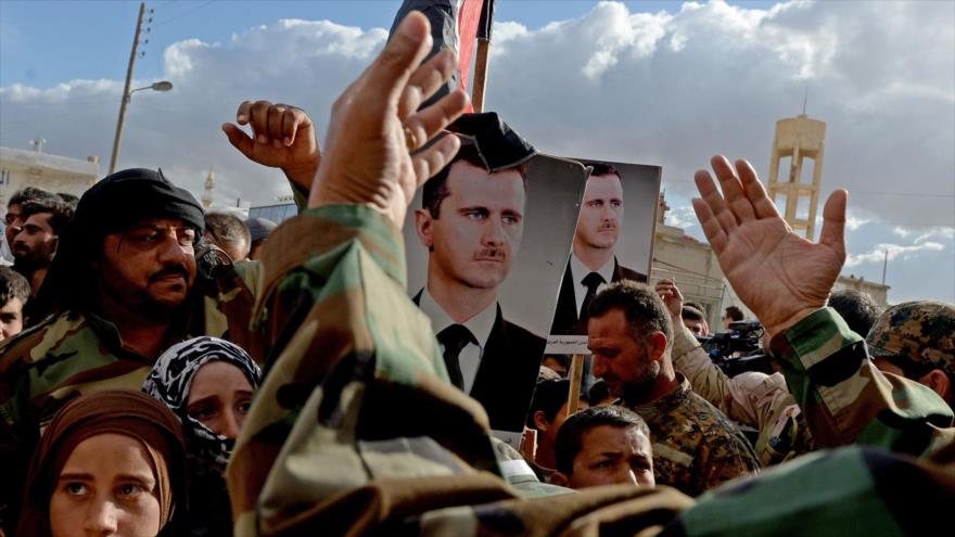 Los sirios, portando imágenes de su presidente, celebran la llegada de un convoy militar a un pueblo cerca de la ciudad de Hama, 4 de mayo de 2016.