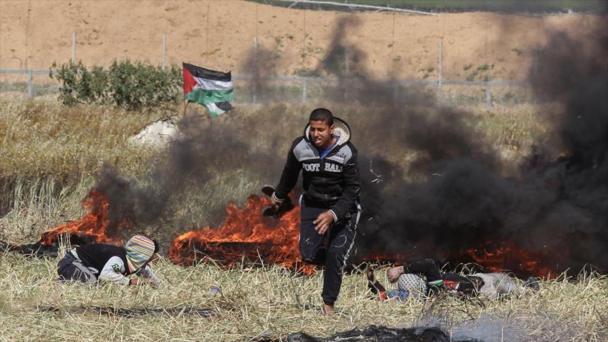 Un palestino busca refugio durante enfrentamientos con fuerzas israelíes luego de la Marcha del Retorno en la Franja de Gaza, 31 de marzo de 2018.