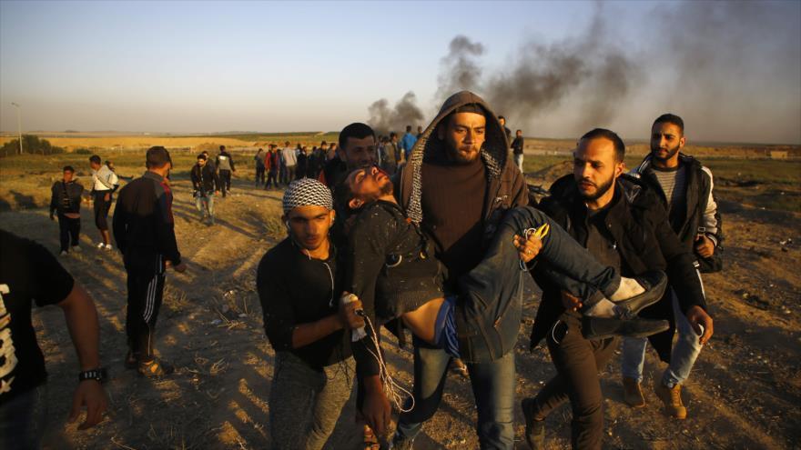 Manifestantes palestinos portan a un herido durante el ataque de las fuerzas de Israel en Gaza, 1 de abril de 2018.