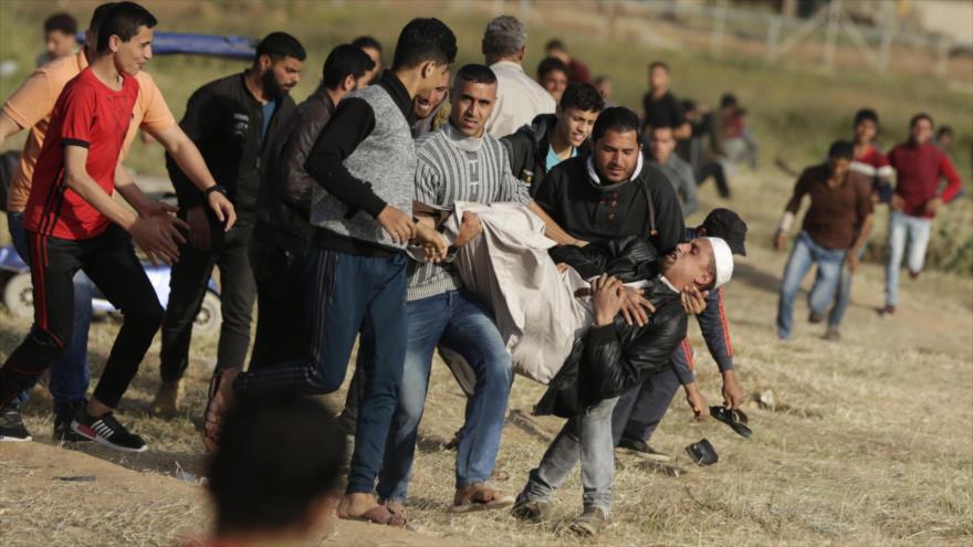 Palestinos llevan en volandas a un hombre herido por los militares israelíes durante una protesta en Gaza a favor del retorno de los refugiados al Estado árabe, 2 de abril de 2018.