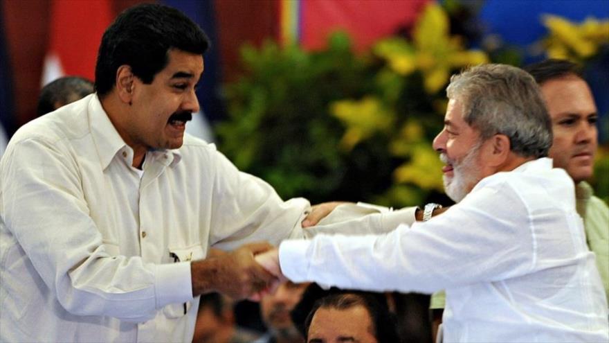 El presidente de Venezuela, Nicolás Maduro (izda.), se da la mano con el exmandatario brasileño Luiz Inácio Lula da Silva.