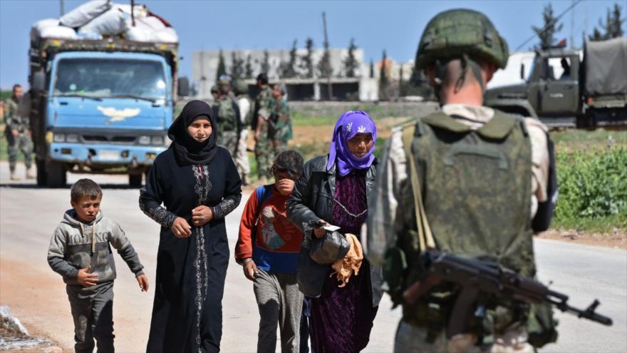 Una familia siria pasa un control gestionado por Rusia de vuelta a su casa desde la provincia de Idlib, controlada por 'rebeldes', 4 de abril de 2018.