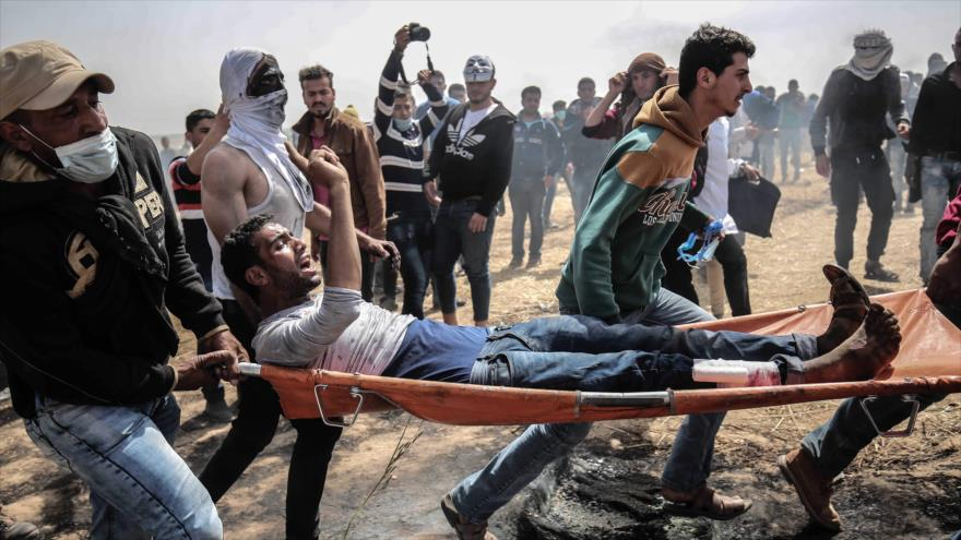 Un palestino herido es socorrido por un grupo de manifestantes en medio de los choques con las fuerzas israelíes en el sur de Gaza, 6 de abril de 2018.