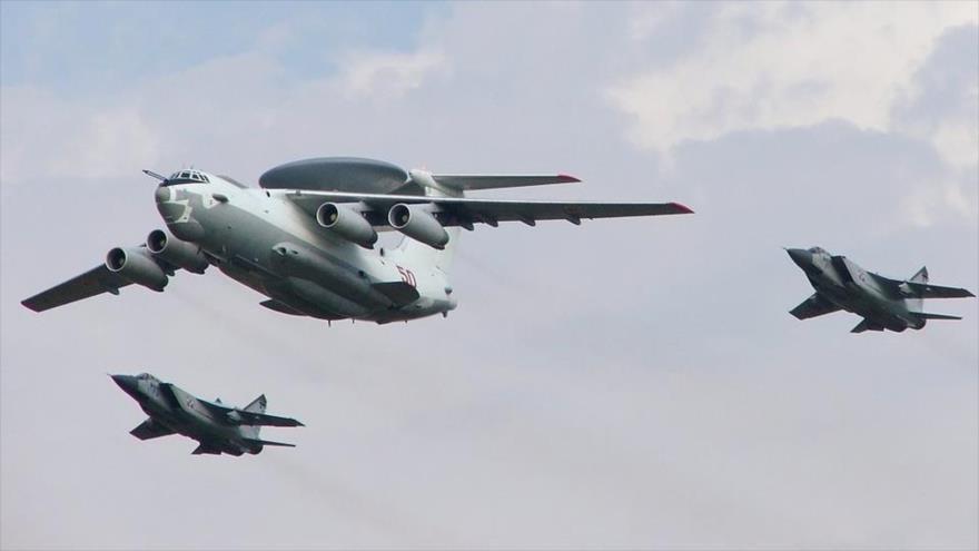Un avión A-50U ruso flanqueado por dos aviones de guerra MiG-31 rusos.