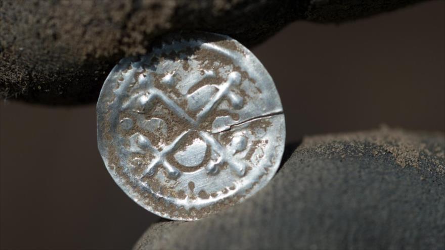 Un arqueólogo muestra una antigua moneda danesa hallada en la isla alemana de Rueguen en el Báltico,13 de abril de 2018.