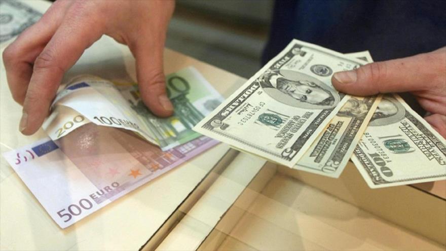 Un hombre cambia billetes de dólar estadounidense (dcha.) con euro.