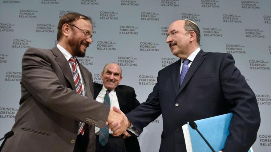 Dore Gold, exembajador israelí ante la ONU (izda.), da la mano a Anwar Majed Eshki, general retirado saudí.
