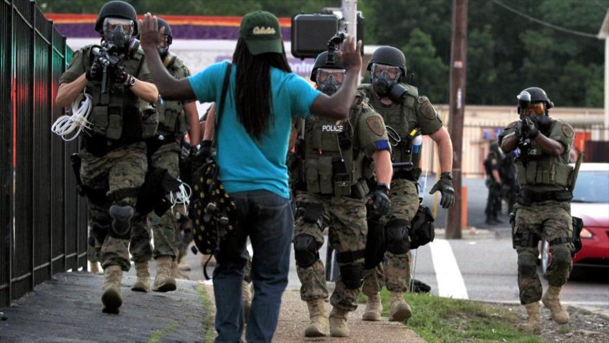 La policía antidisturbios de EE.UU. se enfrenta a un hombre en la ciudad de Ferguson, en el estado estadounidense de Misuri, 11 de agosto de 2014.
