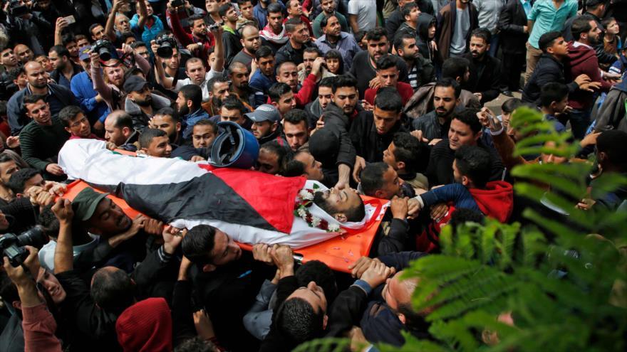 Palestinos llevan el cadáver de un periodista palestino asesinado por tropas israelíes durante protestas en la Franja de Gaza, 26 de abril de 2018.
