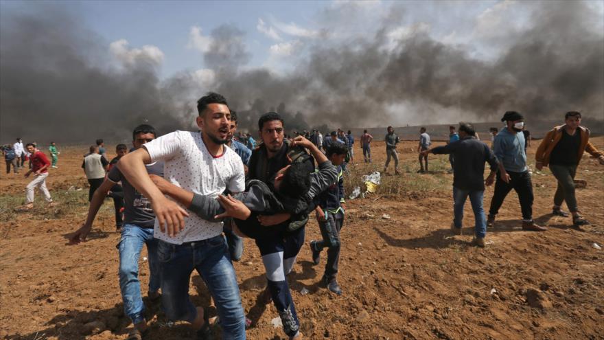 Manifestantes palestinos trasladan a un joven herido por los disparos de soldados israelíes en la Franja de Gaza, 27 de abril de 2018.