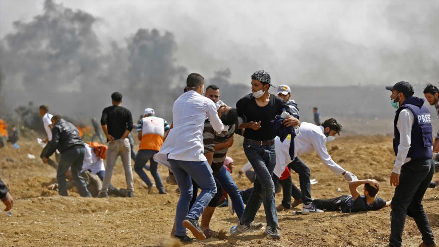 Palestinos llevan a una persona que resultó herida en los enfrentamientos con fuerzas israelíes en la asediada Franja de Gaza, 27 de abril de 2018.