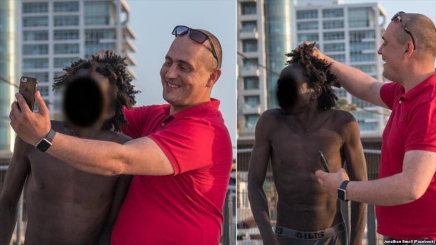 Un israelí se hace selfis humillantes con un migrante africano en una playa de Tel Aviv, 24 de abril de 2018.