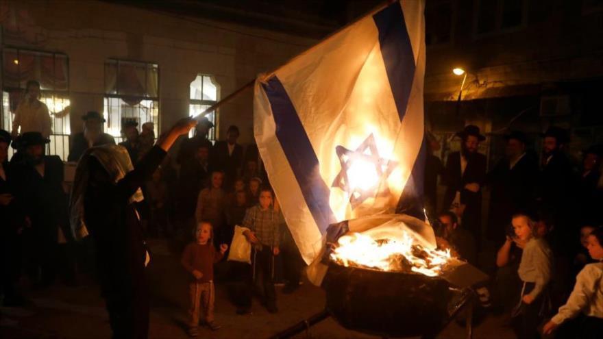 Judíos ultraortodoxos queman una bandera israelí en Al-Quds, 3 de mayo de 2018.