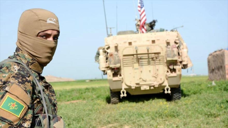 Un miembro de la milicia kurda Unidades de Protección Popular (YPG, por sus siglas en inglés), junto con un vehículo blindado de EE.UU. en Siria.