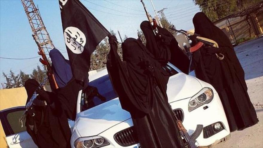 Unas mujeres miembros del grupo terrorista EIIL (Daesh, en árabe) posando con un vehículo BMW M5 y una bandera de Daesh.
