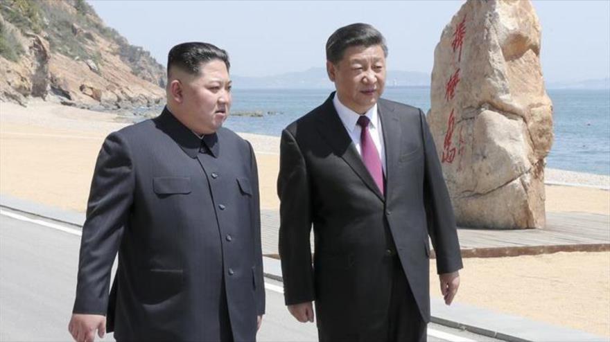 El líder de Corea del Norte, Kim Jong-un (izq.), reunido con el presidente chino, Xi Jinping, en Dalián (China), 8 de mayo de 2018.