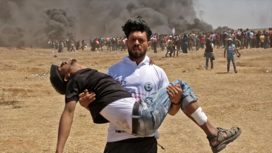 Um palestino carrega um manifestante ferido durante protestos na Faixa de Gaza, reprimido pelas forças israelenses, 14 de maio de 2018.