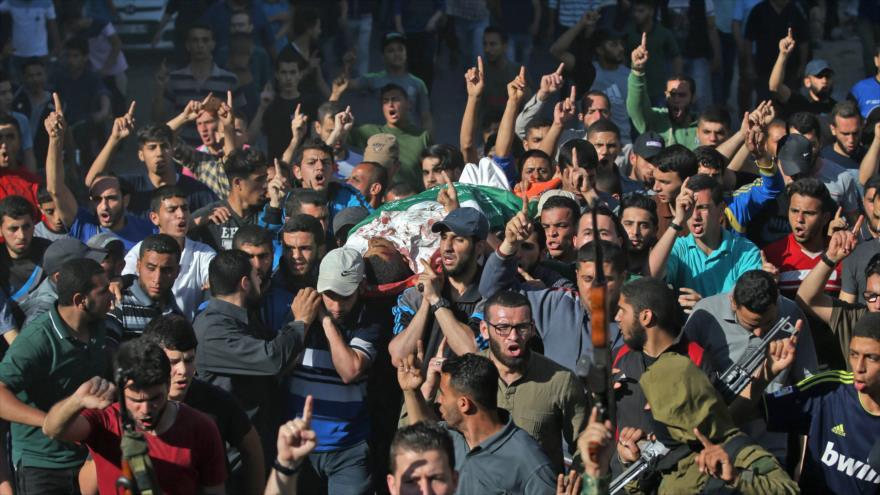 Palestinos participan en el funeral de un hombre que murió por los disparos de las fuerzas israelíes en Gaza, 14 de mayo de 2018.