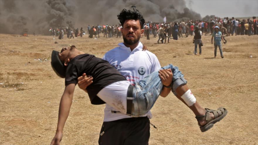 Un palestino traslada a un palestino herido durante las marchas antisraelíes en Gaza, 14 de mayo de 2108.