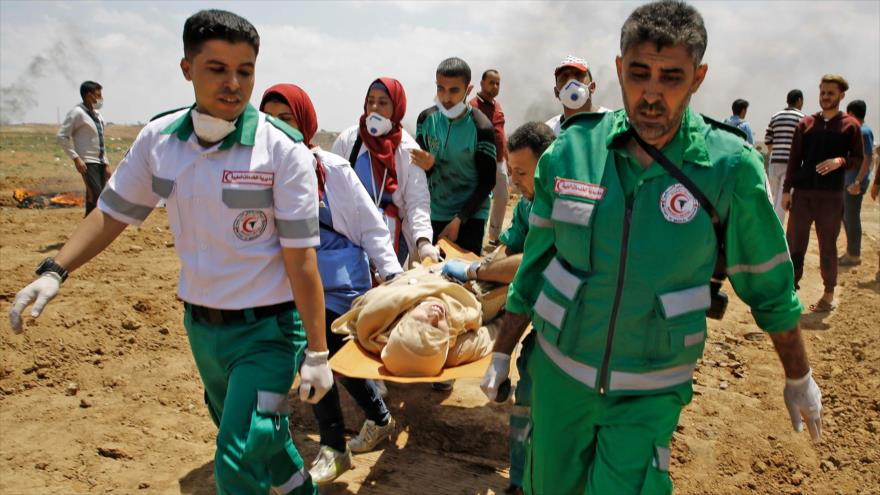 Servicios de emergencia palestinos llevan a una mujer herida por disparos israelíes en una protesta cerca de la frontera de la Franja de Gaza, 14 de mayo de 2018.