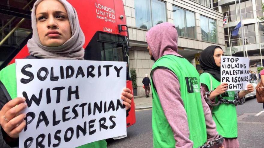 Activistas portan carteles en rechazo a torturas de Israel a prisioneros palestinos.