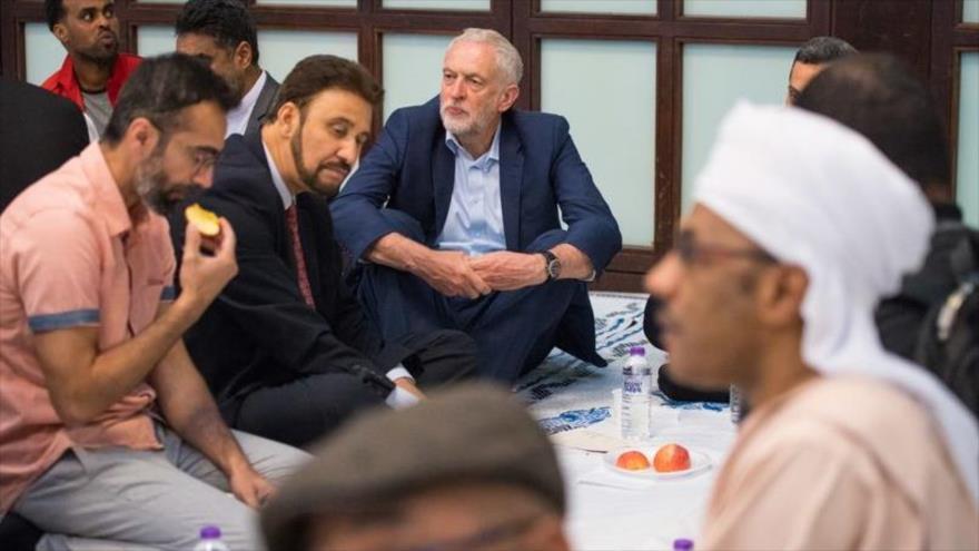 El líder del Partido Laborista británico (PL), Jeremy Corbyn (centro), participa en la ruptura del ayuno en la mezquita de Al-Manaar, Londres, 4 de junio de 2018.