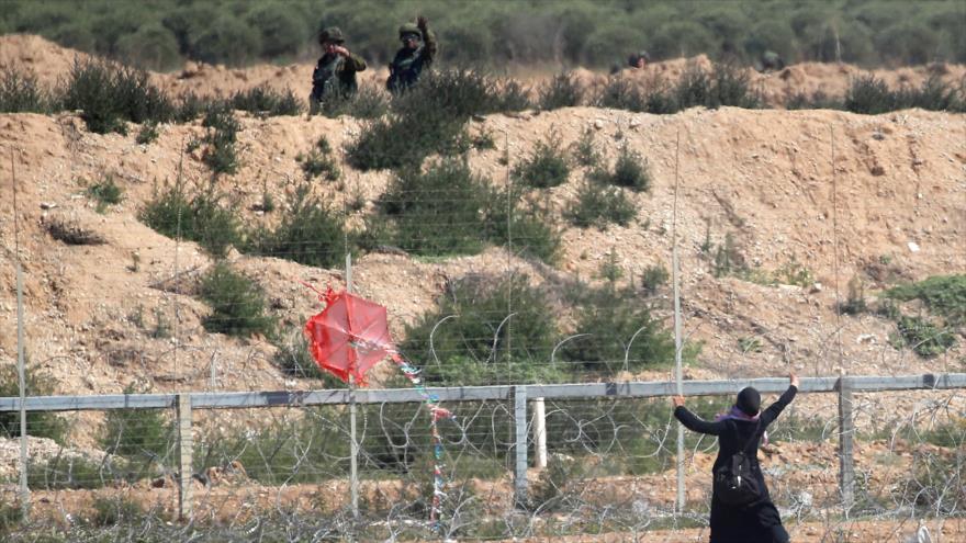 Una mujer palestina intenta volar una cometa en los enfrentamientos con las fuerzas israelíes cerca de los límites de la Franja Gaza e Israel, 14 de mayo de 2018.