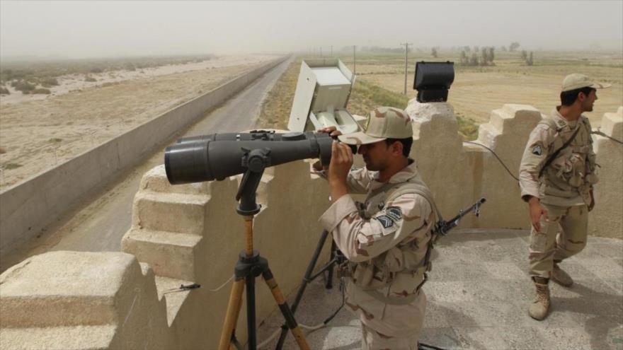 Un guardia fronterizo iraní mira a través de un par de binoculares.