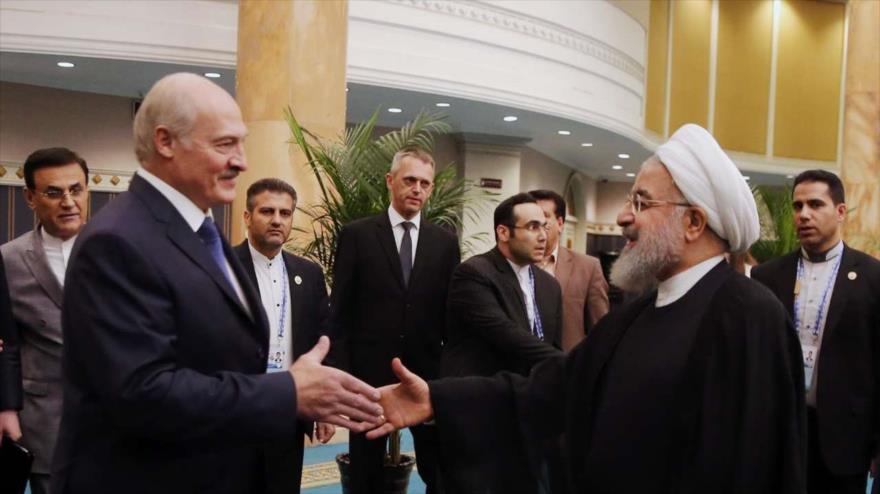 Presidente iraní, Hasan Rohani (dcha.), saluda con su par bielorruso, Alexander Lukashenko, en China, 9 de junio de 2018.