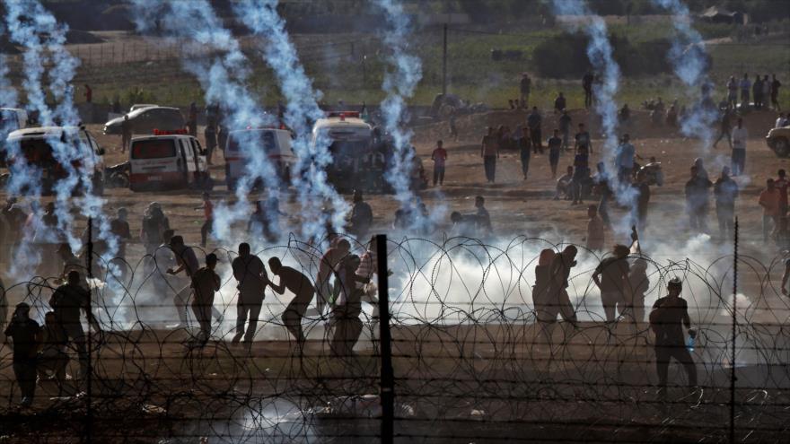 Manifestantes palestinos intentan evadir los gases lacrimógenos lanzados por las fuerzas del régimen israelí en la frontera de la Franja de Gaza.