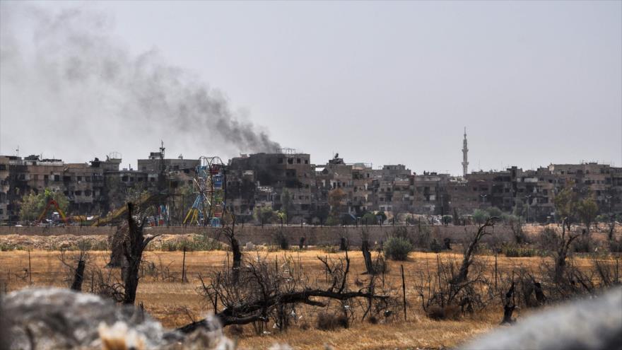 Una imagen tomada durante una gira organizada por el Ejército sirio en la ciudad de Duma, con una columna de humo al fondo, 20 de abril de 2018.