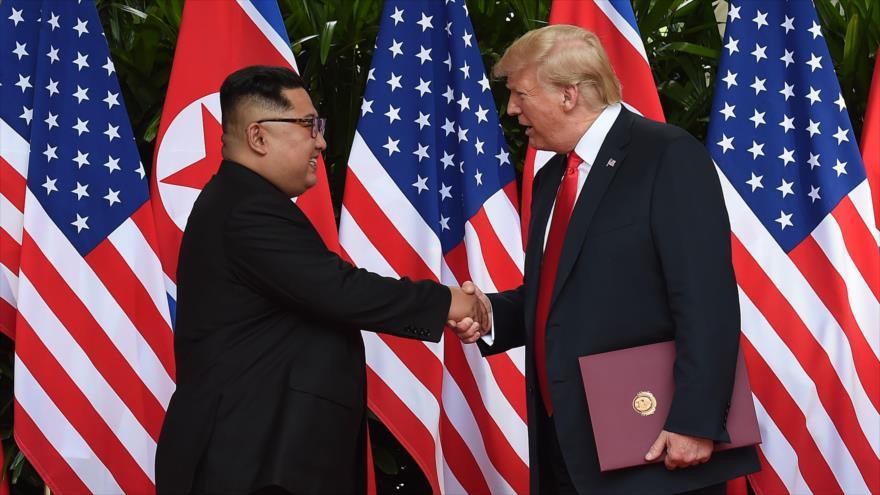 El presidente de EE.UU., Donald Trump (dcha.), y el líder norcoreano, Kim Jong-un, se estrechan la mano tras firma de un documento, 12 de junio de 2018.