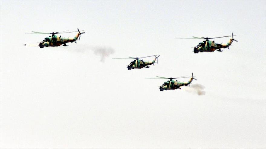 Cuatro helicópteros del Ejército sirio durante lanzan misiles durante una maniobra militar.