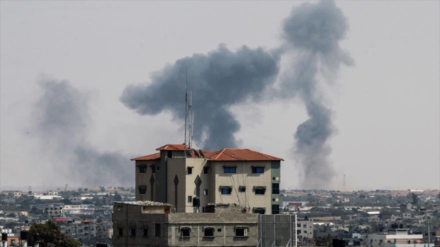 Se ve desde Rafah cómo se levanta humo sobre los edificios tra un ataque aéreo israelí en La Franja de Gaza, 9 de mayo de 2018.