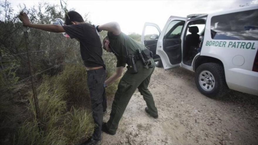 Un agente de la Policía de EE.UU. registra a un inmigrante indocumentado en Texas.