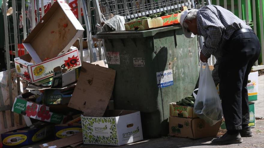 Un israelí rebusca comida en la basura, 24 de junio de 2015.