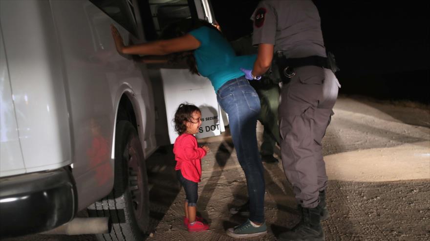 Un agente fronterizo de EE.UU. revisa a una inmigrante en presencia de su hija, 12 de junio de 2018.