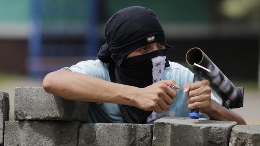 Un manifestante antigubernamental se prepara para disparar su mortero, la localidad de Masaya, Nicaragua, 19 de junio de 2018.