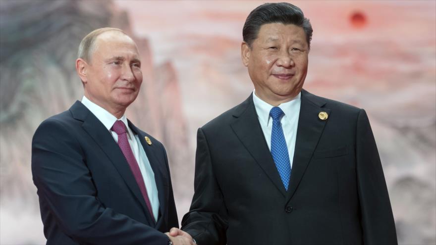 El presidente ruso, Vladimir Putin, (izq.), estrecha la mano de su par chino, Xi Jinping, en un evento en Qingdao, China, 10 de junio de 2018.