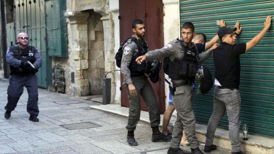 Las fuerzas de seguridad israelíes realizan un registro corporal a dos palestinos en la ciudad ocupada palestina de Al-Quds (Jerusalén).