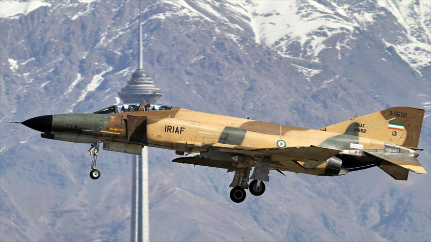 Un caza F-4 Phantom de Irán vuela cerca del torre de Milad en Teherán, la capital iraní.