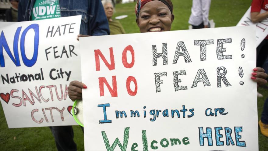 Una mujer sostiene un cartel durante una manifestación de apoyo a las familias migrantes que han sido separadas.