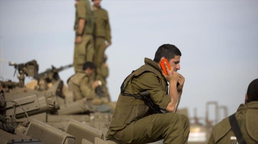 Un soldado del régimen de Israel usando su teléfono móvil.