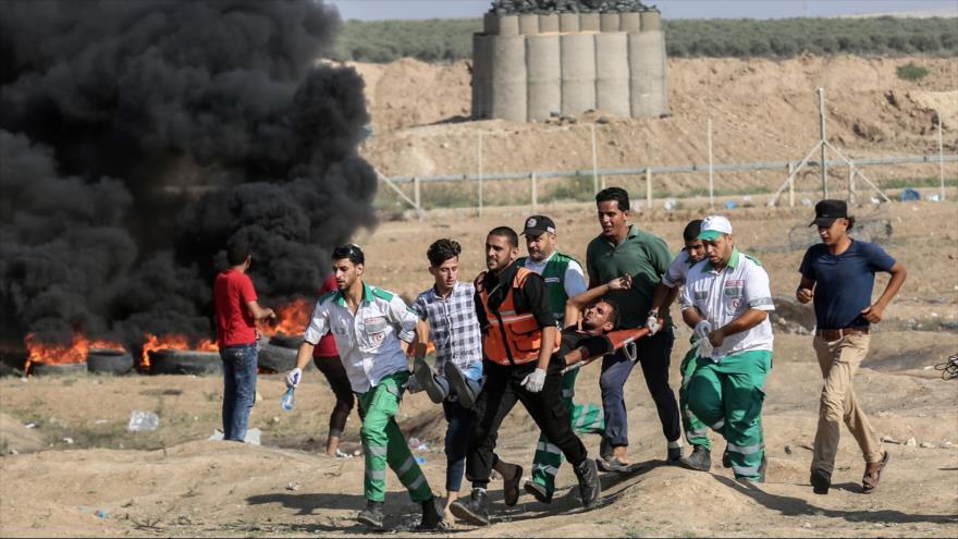 Los médicos trasladan a un adolescente palestino herido por las fuerzas israelíes en el este de la Franja de Gaza, 6 de julio de 2018.